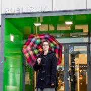 Kuvassa erikoistutkija Mona Mannevuo Publicum-rakennuksen edustalla sateenvarjo kädessä