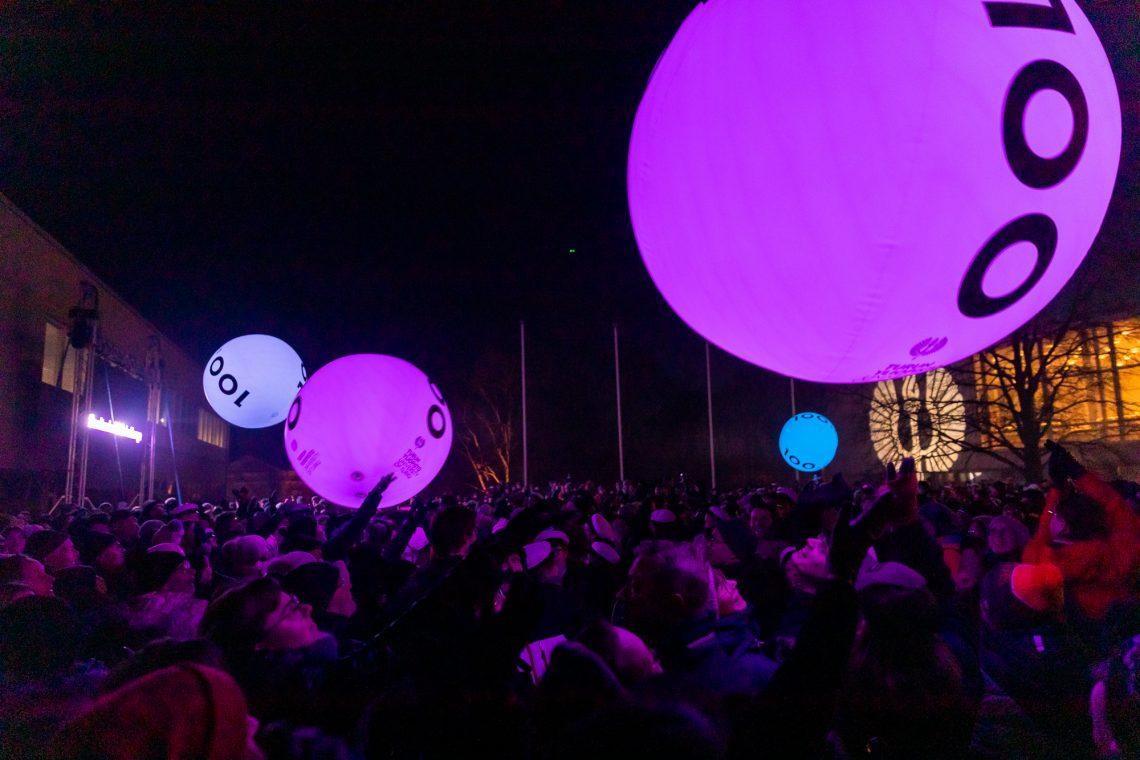 Yleisö heittelemässä isot ledvalaistuja 100-logoisia palloja.