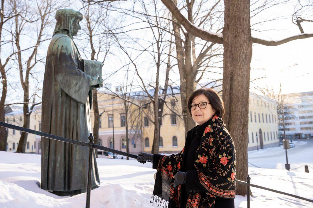 Kaisa Häkkinen kuvattuna Mikael Agricolan patsaan edessä Turussa