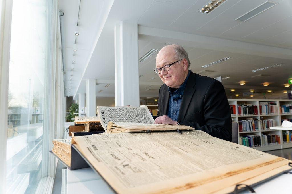 Hannu Salmi selaamassa vanhoja sanomalehtiä